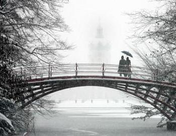 People walk over a bridge in the grounds of the Charlottenburg Castle during heavy snowfall in Berlin